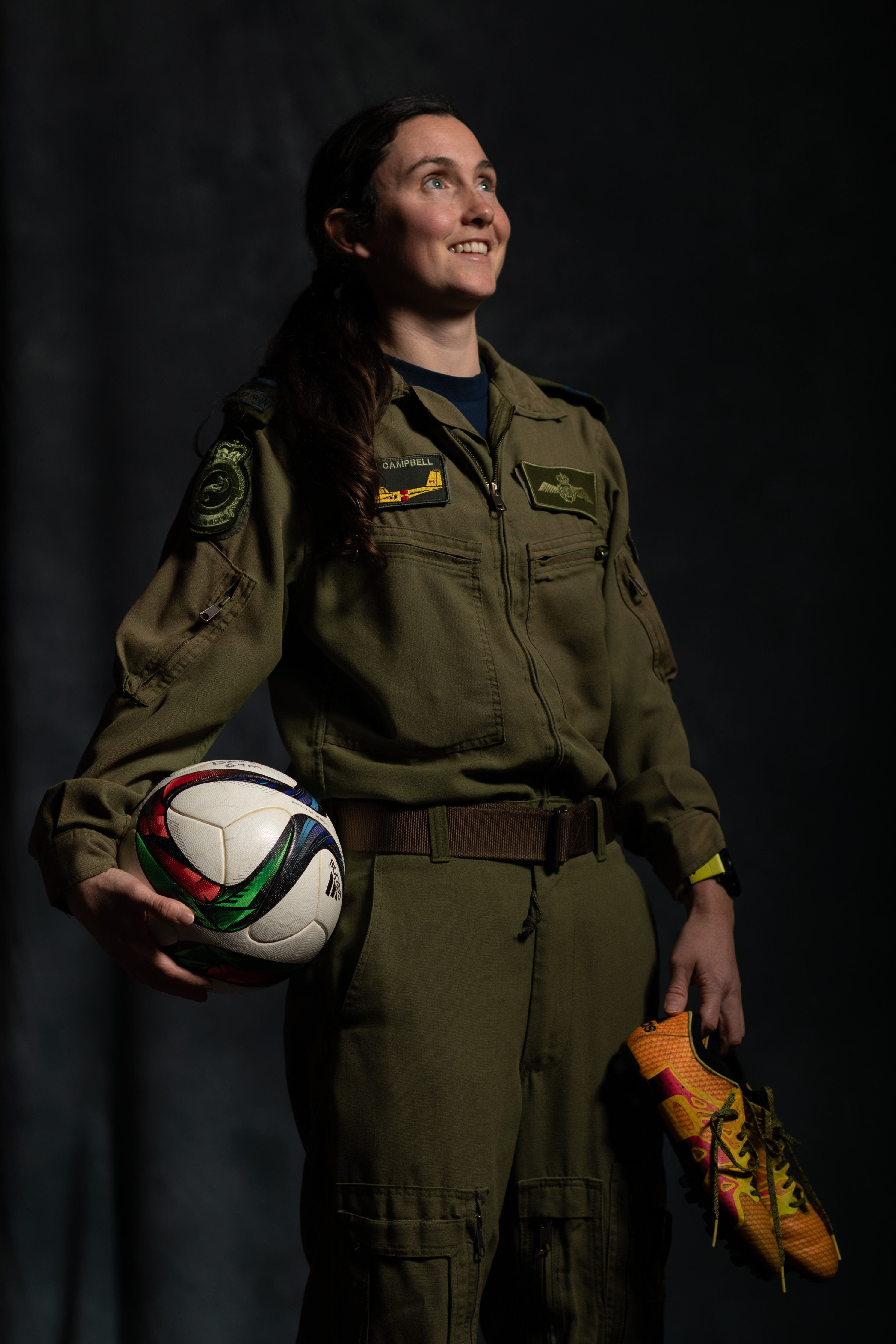 A smiling woman wearing an olive-green flight suit and holding a ball and sports shoes.