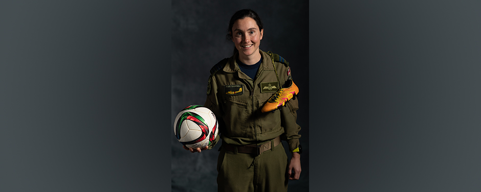 slide - A smiling woman wearing an olive-green flight suit and holding a ball and sports shoes.