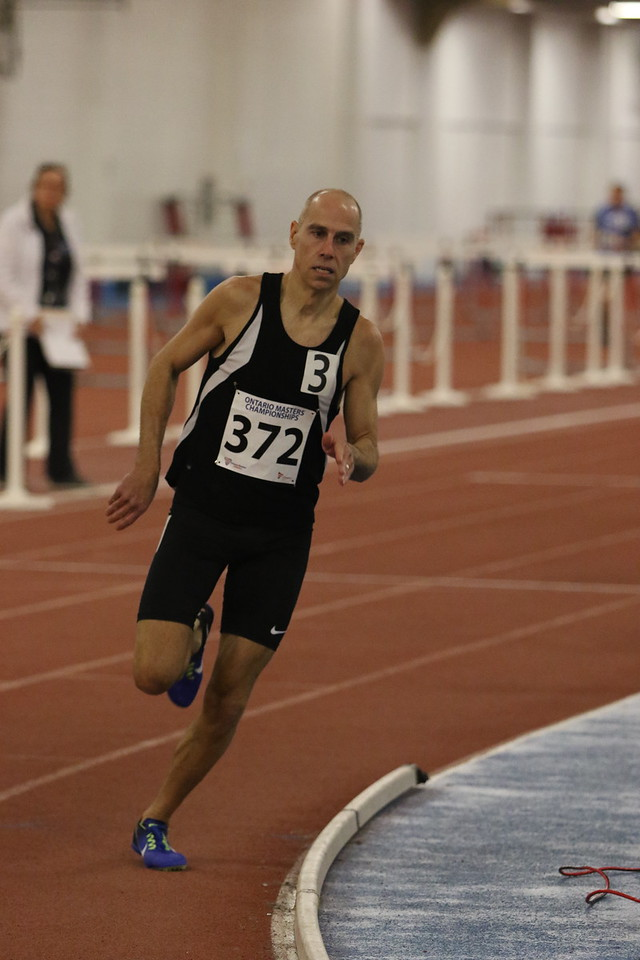 A man wearing black shorts and a black bib showing number 372 runs on an indoor track.