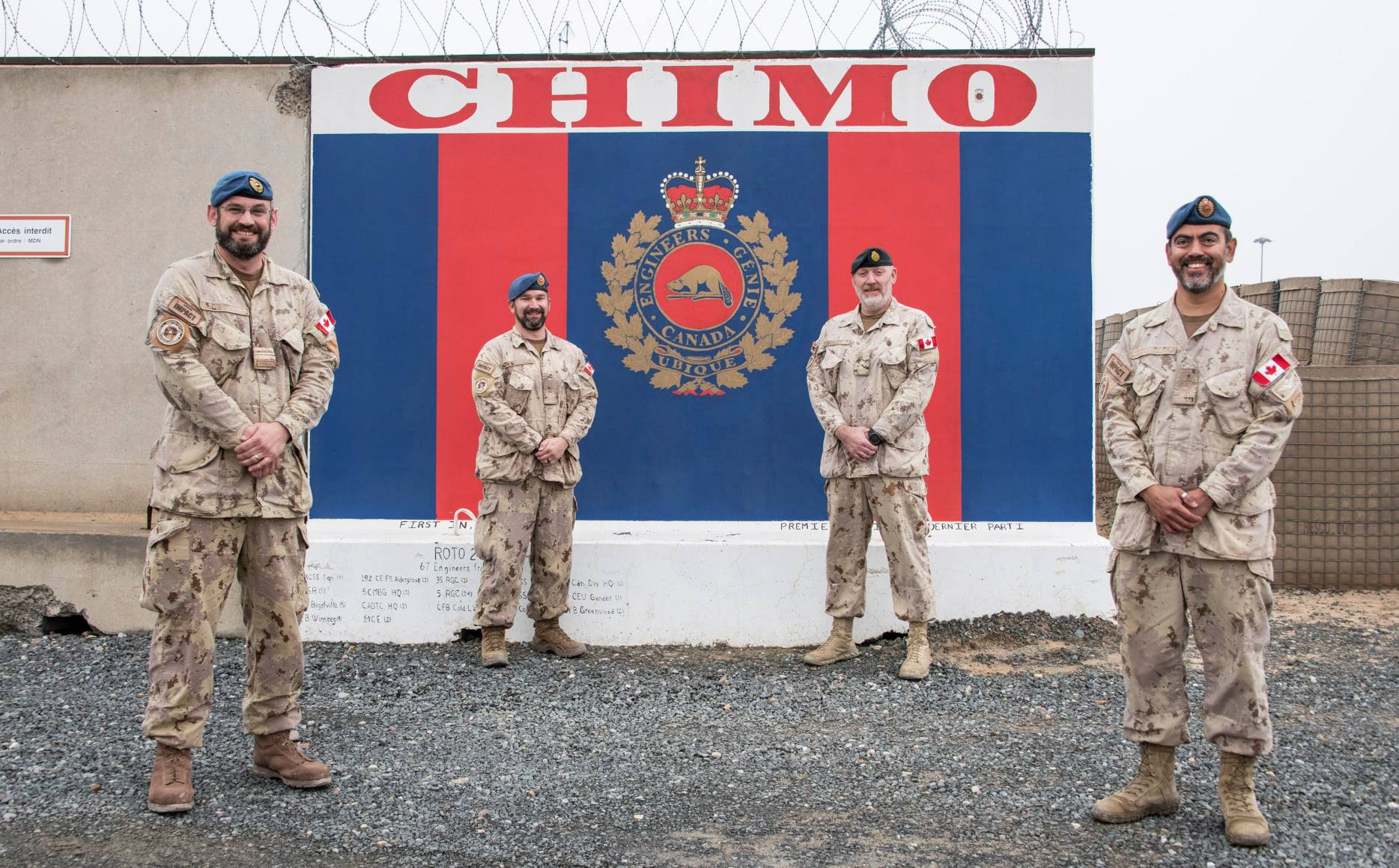 Master Warrant Officer (MWO) Edward Hebb (second from left), Engineer Sergeant Major and Plans MWO, Operation Support Hub – South West Asia (OSH-SWA), with Major Christopher Greaves, Joint Task Force – IMPACT Engineer, Officer in Charge, Lieutenant-Colonel Stéphane Roussel, and MWO Mario Rosales, Commanding Officer and Sergeant Major of OSH-SWA, in front of the Construction Engineering wall in Camp Canada, at Ali Al Salem Air Base, Kuwait, on December 4, 2020, after MWO Hebb learned that Governor General Julie Payette had awarded him the Order of Military Merit. PHOTO: Sailor Third Class Melissa Gonzalez