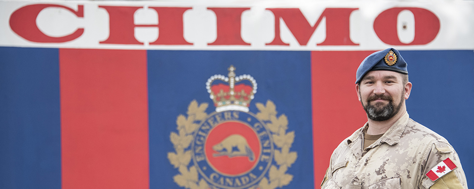 "slide - A man wearing a combat uniform stands in front of a wall with vertical blue and red stripes, the Canadian Armed Forces' engineers' crest and the word ""CHIMO""."