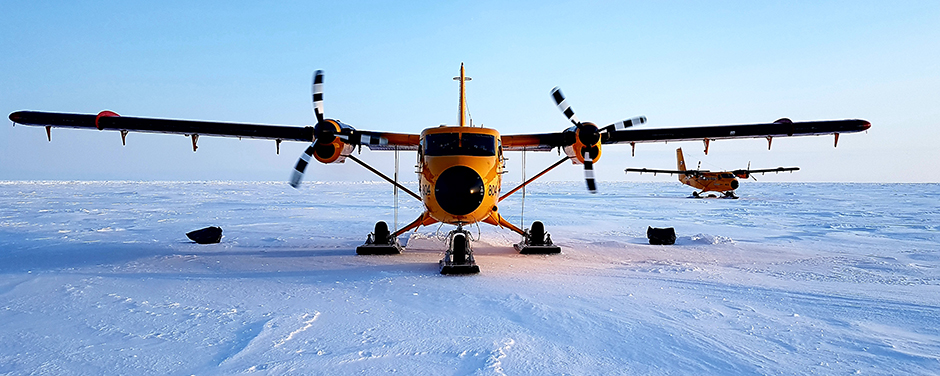 slide - Two orange twin-propeller aircraft equipped with skis on snow in the Arctic.