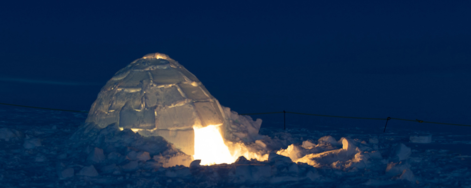 slide - A photo of an illuminated igloo at night.