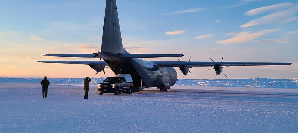 Two people stand in front of a pickup truck and a big grey propeller aircraft in an Arctic landscape.