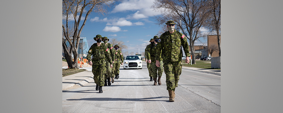 slide - A group of people wearing green camouflage uniforms and hats march in rows in the street.